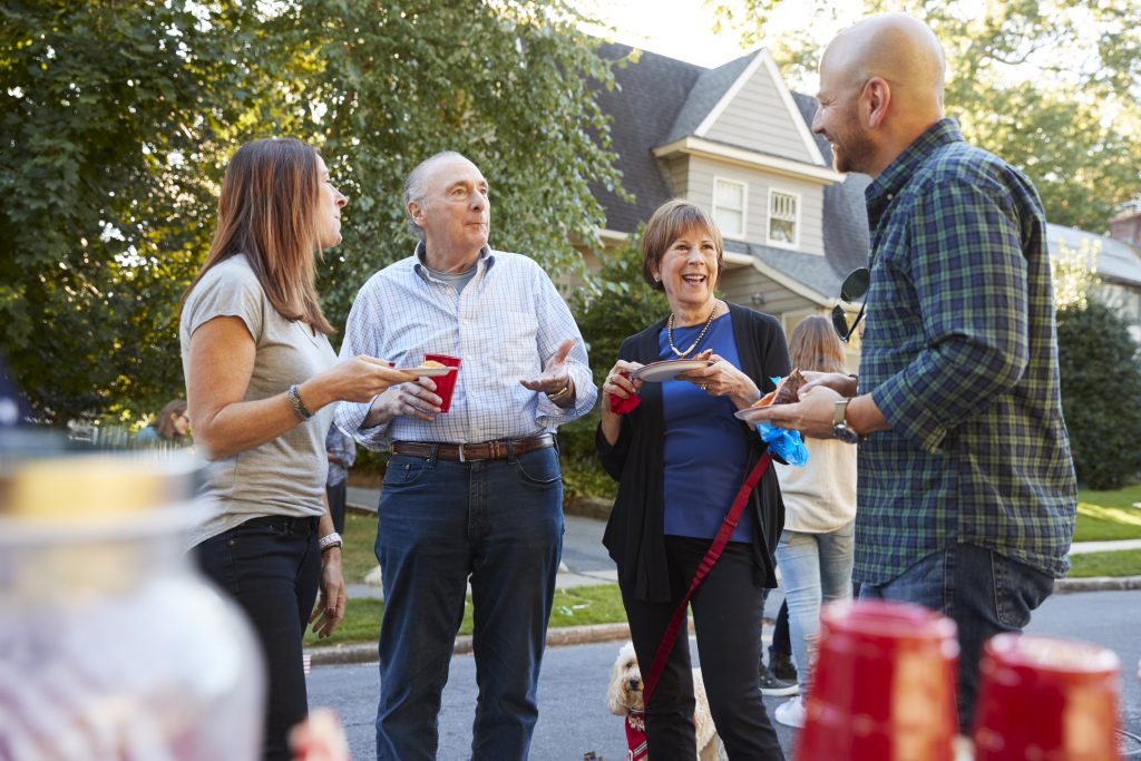 Middle aged and senior neighbours talking at a block party